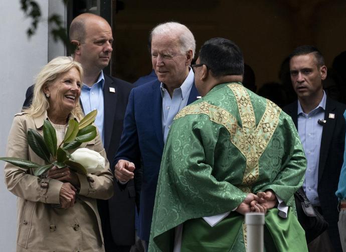 Joe Biden parla con un prete dopo la messa